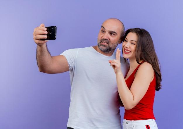Glückliches erwachsenes paar, das selfie-frau macht friedenszeichen nimmt