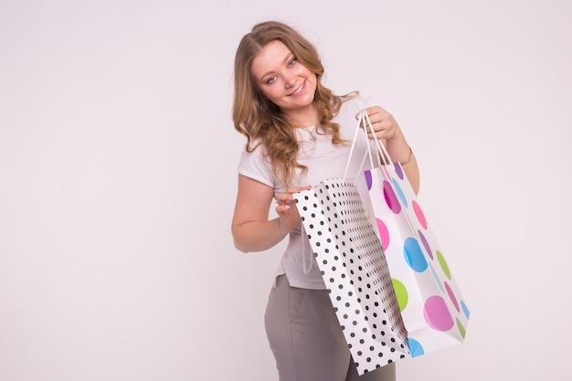 Glückliches europäisches blondes mädchen mit farbigen einkaufstaschen auf weiß mit kopienraum.