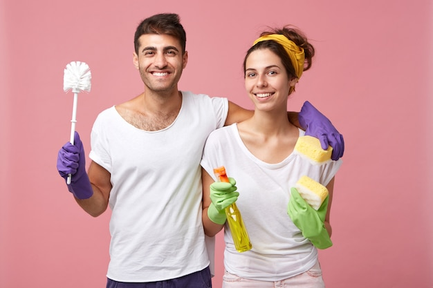 Glückliches europäisches paar mit schwamm, waschmittel und bürste, die gute laune vor dem frühjahrsputz umarmen, gute beziehungen haben und hausarbeit zusammen machen. hausputz- und teamwork-konzept
