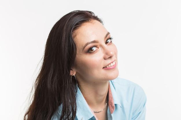 Glückliches europäisches weibliches modell mit dunklen haaren. porträt der verträumten jungen frau im blauen hemd lokalisiert auf weißem hintergrund.