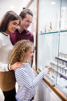 Glückliches familieneinkaufen im juweliergeschäft