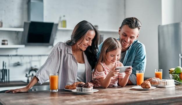 Glückliches familienkonzept in der küche. das süße kleine mädchen und ihre schönen eltern benutzen ein smartphone und lächeln, während sie sich auf ein köstliches frühstück vorbereiten.