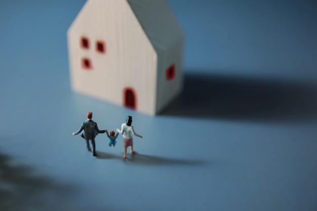 Glückliches familienkonzept. miniaturfigur von vater, mutter und sohn, die hände halten und ins haus gehen
