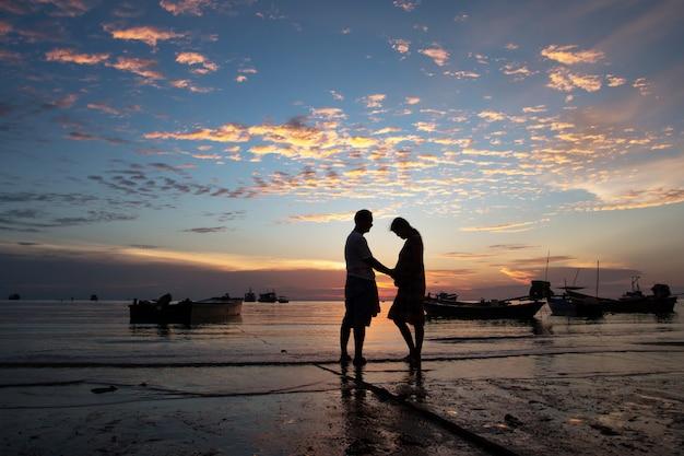 Glückliches familienkonzept, paar am strandsonnenunterganghintergrund