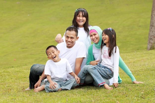 Glückliches familienlächeln einer mutter und eines vaters mit ihren kindern