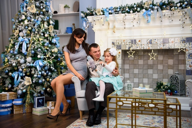 Glückliches familienpaar gibt geschenke im wohnzimmer, hinter dem geschmückten weihnachtsbaum, das licht gibt eine gemütliche atmosphäre.