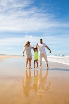 Glückliches familienpaar und kleines mädchen, das das gehen und die aktivitäten am strand genießt, kind, das elternhände hält, springt und hängt