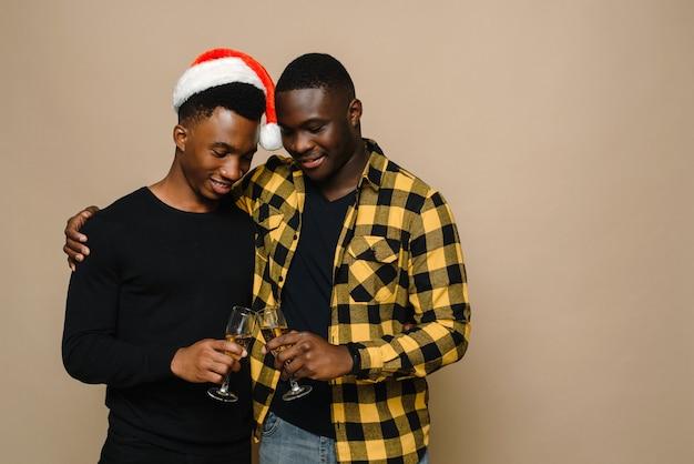 Glückliches familienporträt an weihnachten, schwules männliches paar auf beigem hintergrund.