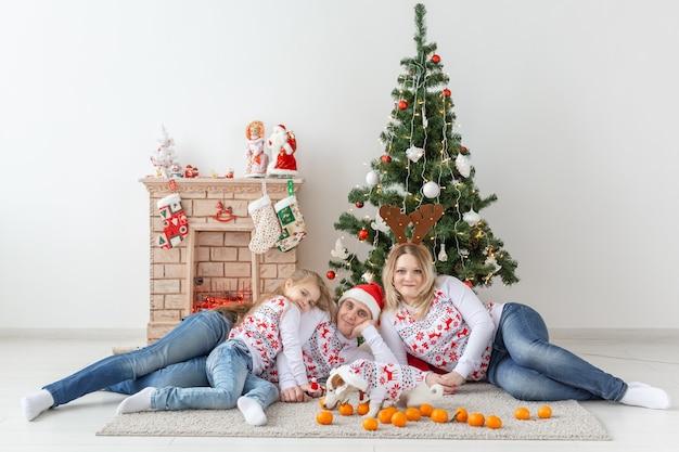 Glückliches familienporträt durch weihnachtsbaum