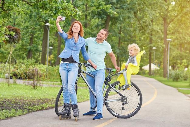 Glückliches familienreitfahrrad am park