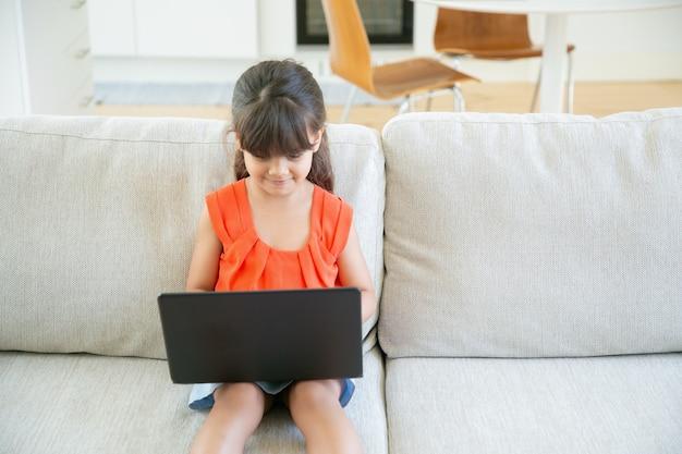 Glückliches fokussiertes kleines kind, das laptop alleine benutzt. nettes mädchen, das auf couch sitzt und cartoons auf pc beobachtet