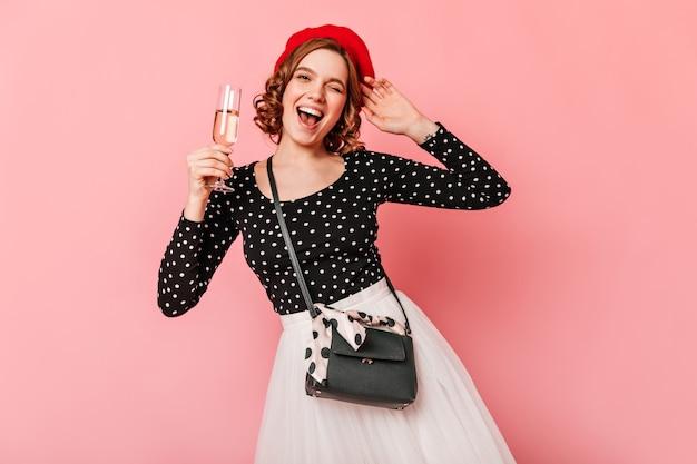 Glückliches französisches mädchen, das weinglas hält. studioaufnahme der lächelnden lockigen frau in der baskenmütze lokalisiert auf rosa hintergrund.