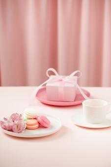 Glückliches frauen- / muttertagsbild einer kaffee- oder teetasse und einer lisianthus-blume mit makronen und geschenken daneben auf rosa vorhängen.