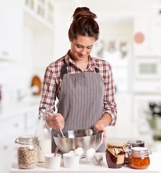Glückliches frauenbacken in ihrer küche
