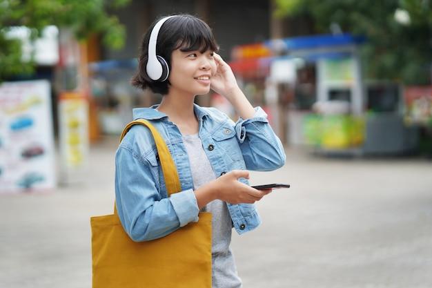 Glückliches fraueneinkaufen mit dem hören von musik auf smartphone und dem halten der einkaufstasche