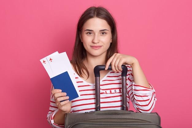 Glückliches frauenmädchen mit koffer, ticket und pass posiert lokalisiert über rosa hintergrund,