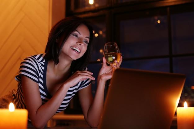 Glückliches frauenporträt mit glas wein, der pc-bildschirm betrachtet