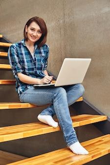 Glückliches freiberufliches mädchen, das an laptop am hausförster arbeitet. arbeite als freiberufler, free crapher, traumjob, eigenes unternehmen