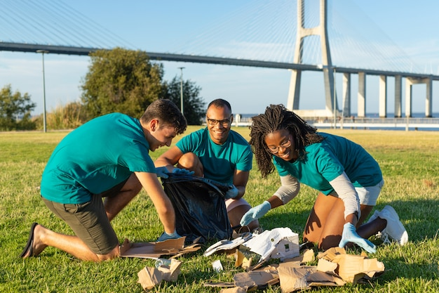 Glückliches freiwilliges team, das grünen stadtbereich säubert