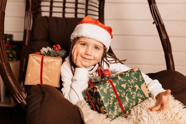 Glückliches freudiges kleines mädchen, das weihnachtsmütze trägt, der mit weihnachtsgeschenken aufwirft