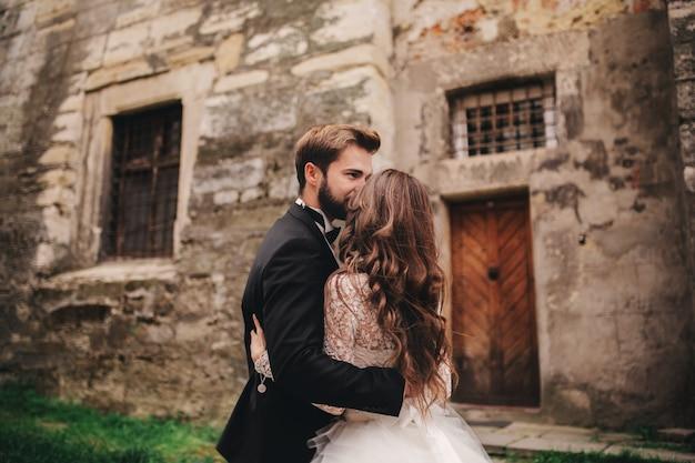Glückliches frisch verheiratetes paar, das in der alten europäischen stadtstraße umarmt und küsst, herrliche braut im weißen hochzeitskleid zusammen mit hübschem bräutigam. hochzeitstag.