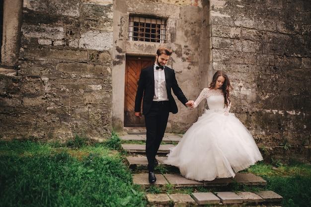 Glückliches frisch verheiratetes paar, das in der alten europäischen stadtstraße umarmt und küsst