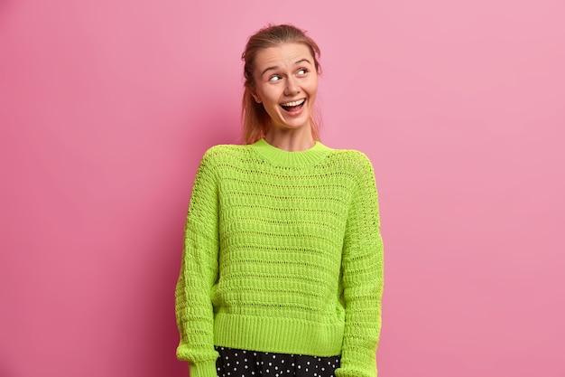 Glückliches fröhliches europäisches tausendjähriges mädchen im grünen strickpullover, das mit zahnigem lächeln beiseite fokussiert wird, genießt das leben, kichert über etwas positives, bemerkt richtig etwas komisches