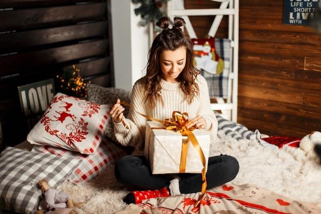 Glückliches fröhliches junges mädchen in einem gestrickten weinlesepullover öffnet ein geschenk auf einem bett am heiligabend