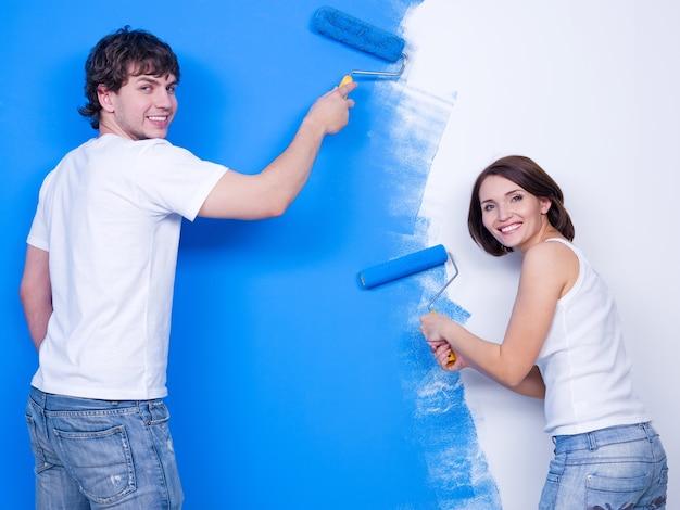 Glückliches fröhliches junges paar, das die wand in der blauen farbe bürstet