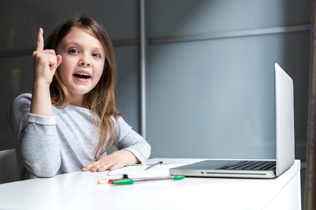 Glückliches fröhliches mädchen, das mit einem laptop am schultisch sitzt