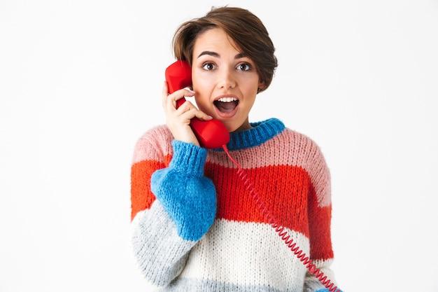 Glückliches fröhliches mädchen, das pullover trägt, der lokal auf weiß steht und auf einem festnetztelefon spricht