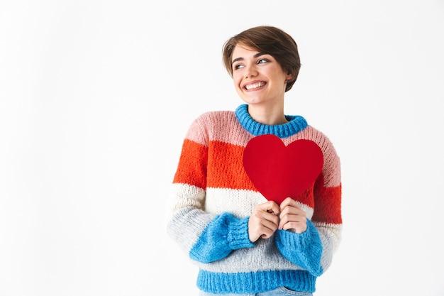 Glückliches fröhliches mädchen, das pullover trägt, der lokal auf weiß steht und rotes herz hält
