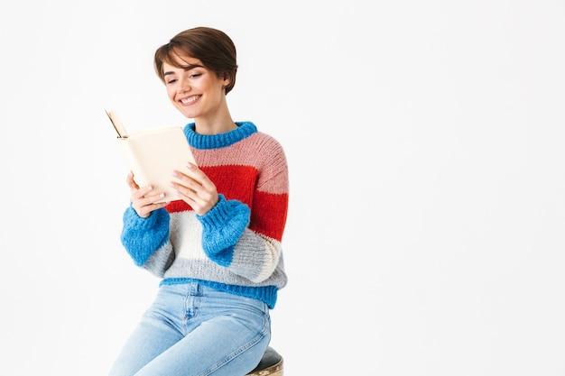 Glückliches fröhliches mädchen, das pullover trägt, sitzt auf einem stuhl lokalisiert auf weiß, liest ein buch