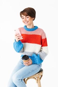Glückliches fröhliches mädchen, das pullover trägt, sitzt auf einem stuhl lokalisiert auf weiß, unter verwendung des mobiltelefons, hält tasse zum mitnehmen