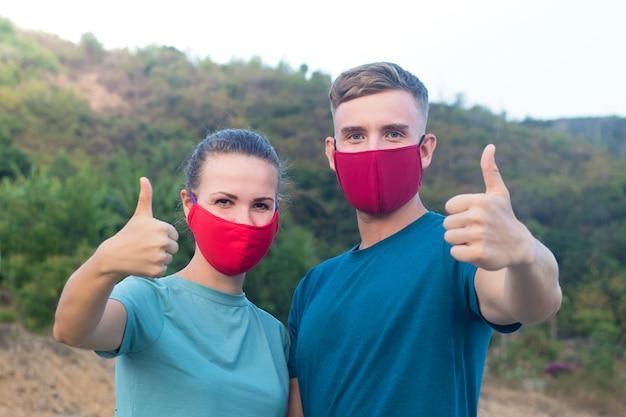 Glückliches fröhliches paar, mann, mädchen, mann und frau in schutzmaske zeigen daumen auf, wie geste. luftverschmutzung, virus, chinesisches pandemie-coronavirus-schutzkonzept. 2019-ncov.