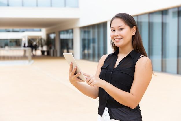 Glückliches frohes studentenmädchen mit dem tablettenlächeln