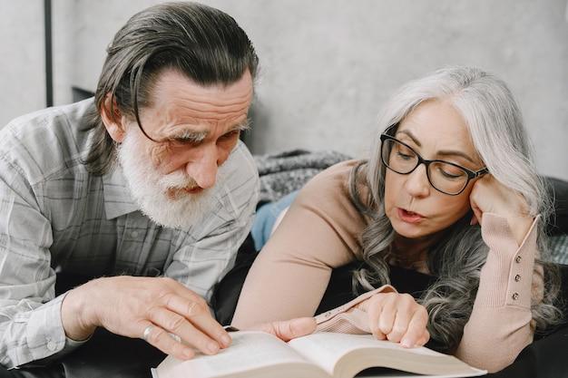 Glückliches gealtertes ehepaar, das sich zu hause zusammen entspannt. älteres paar liest buch auf dem bett.