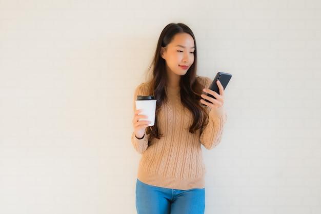 Glückliches gebrauchsmobiltelefon des schönen jungen asiatischen frauenlächelns des porträts