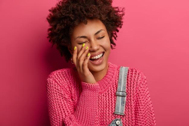 Glückliches gefühls- und gefühlskonzept. freudige lockige afroamerikanerin lacht aus, als sie einen lustigen witz hört, lächelt breit, wird von einem lustigen freund unterhalten, lässig gekleidet, posiert drinnen
