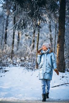 Glückliches gehen der frau in einen winterpark
