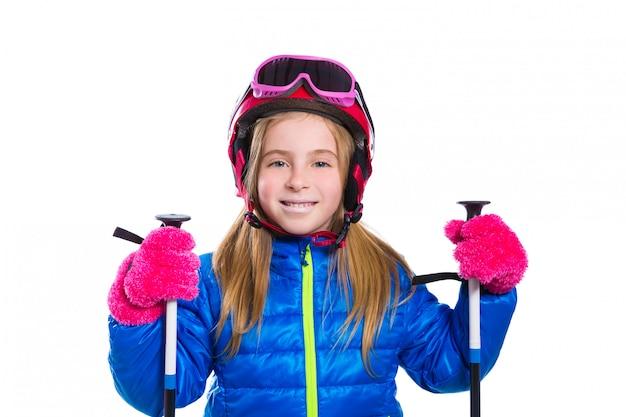 Glückliches gehen des blonden kindermädchens, mit skistöcken und sturzhelm zu schneien