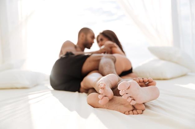 Glückliches gemischtrassiges paar, das am weißen strandbett liegt und umarmt
