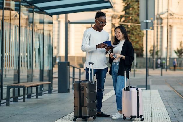 Glückliches gemischtrassiges paar schaut auf bordkarte, die abflugzeit an der haltestelle in der nähe des flughafens überprüft.