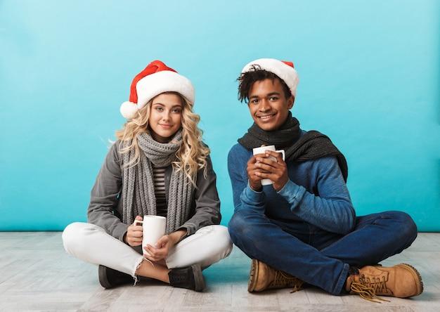 Glückliches gemischtrassiges teenagerpaar, das isoliert über blauer wand sitzt, weihnachtsmützen trägt, tassen hält