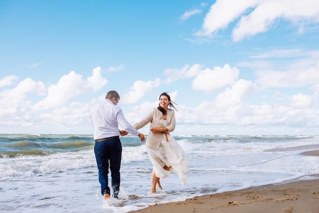 Glückliches gerade verheiratetes paar mittleren alters gehen am strand gegen blauen himmel mit clouns und haben spaß am sommertag.