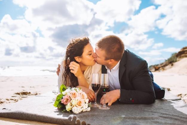 Glückliches gerade verheiratetes paar mittleren alters gehen am strand spazieren, küssen sich und haben spaß am sommertag.