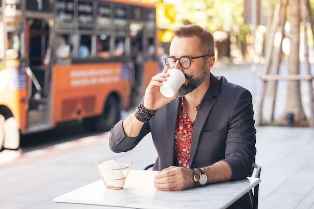 Glückliches geschäftsmannporträt mittleren alters, das einen kaffee draußen trinkt