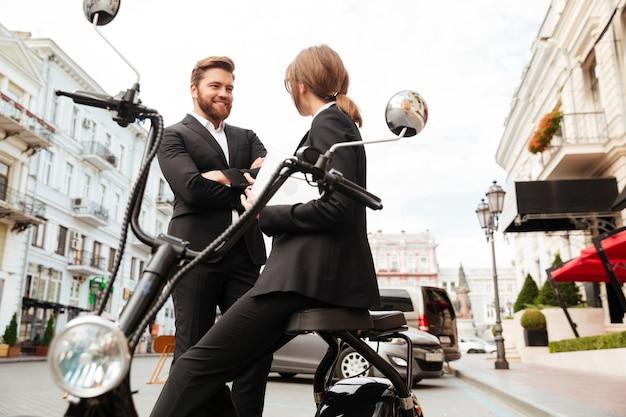 Glückliches geschäftspaar, das nahe dem modernen motorrad draußen aufwirft