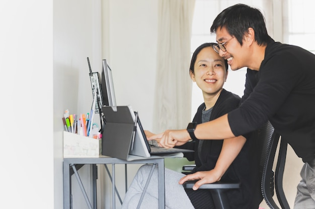 Glückliches geschäftspaar, das zu hause am computer zusammenarbeitet.