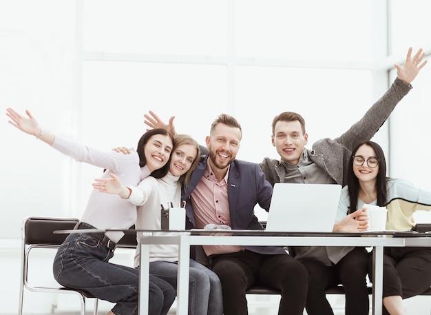Glückliches geschäftsteam, das am schreibtisch sitzt. das konzept der teamarbeit